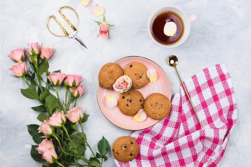 杯子红茶、曲奇饼、桃红色玫瑰毛巾和花束  免版税库存照片