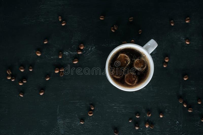 杯子顶视图在黑暗的桌面的冷的被冰的咖啡用烤咖啡豆 免版税库存图片