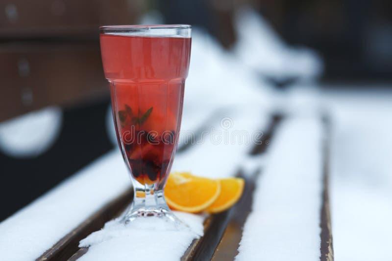 杯季节性热的维生素饮料在一个长木凳的雪站立在一寒冷冬天天 免版税库存照片