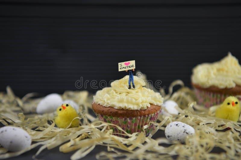 杯形蛋糕冠上了与拿着标志的一个微型人小雕象表明i爱复活节与有些装饰 免版税库存照片
