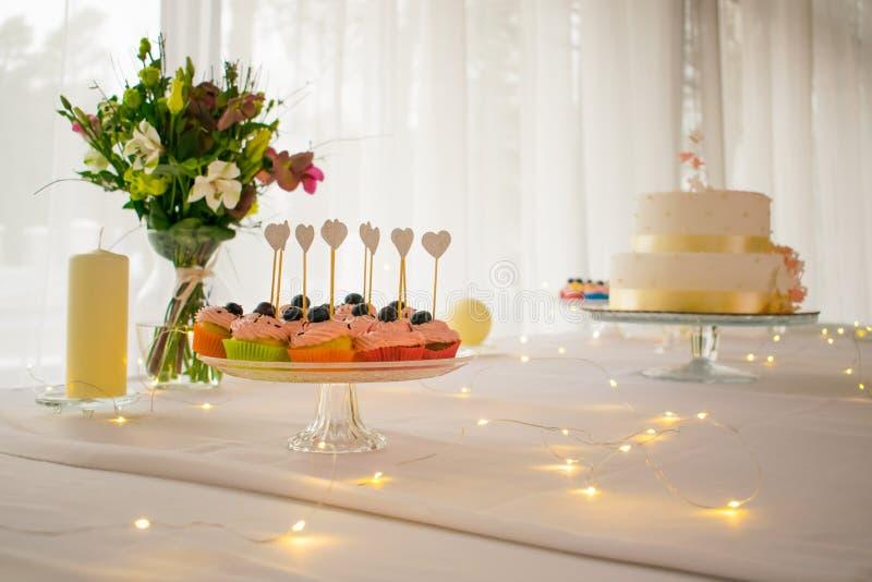 杯形蛋糕和花与被带领的光在白色桌装饰 免版税库存图片