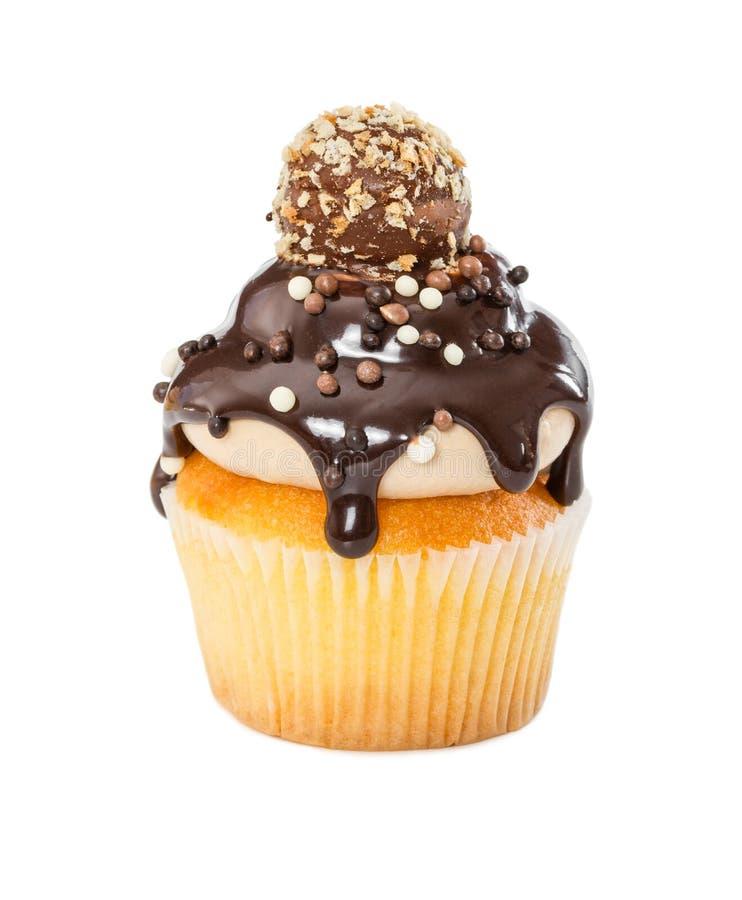 杯形蛋糕用巧克力糖浆,洒和在wh隔绝的糖果 库存照片