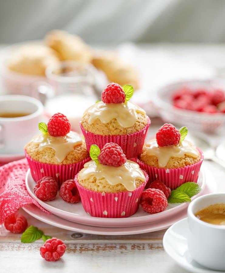 杯形蛋糕用白色巧克力和新鲜的莓在一块陶瓷板材在一张木白色桌上,关闭 库存图片