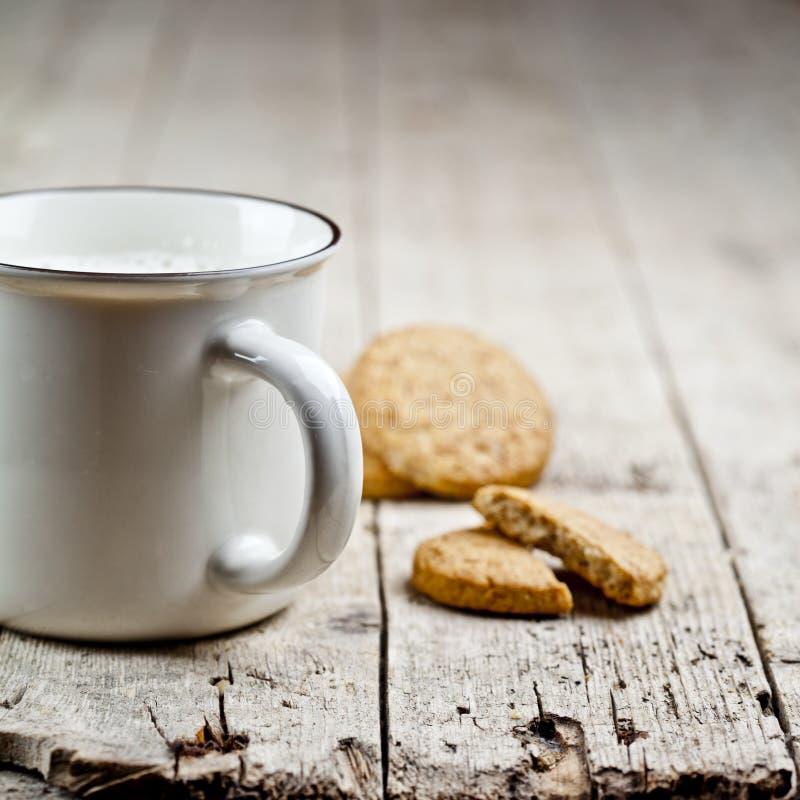 杯新鲜的牛奶和一些自创被烘烤的燕麦曲奇饼在土气木桌背景 库存照片