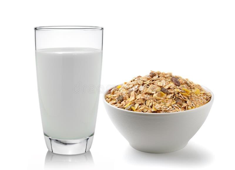 杯新鲜的牛奶和muesli在白色bac用早餐安置 免版税库存照片