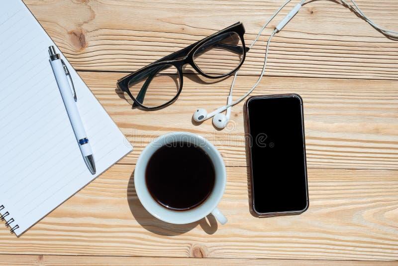 杯无奶咖啡和巧妙的电话有办公用品的;在蓝色木桌背景的笔、笔记本和眼睛玻璃 免版税库存图片