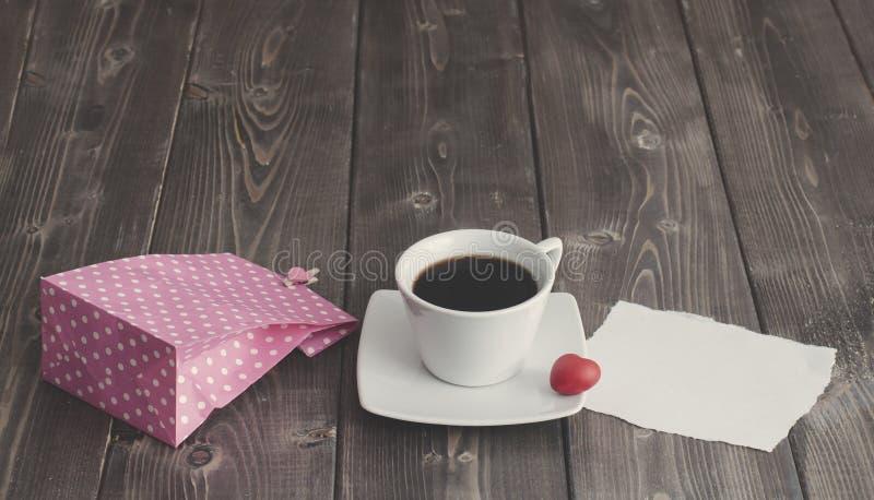 杯无奶咖啡,桃红色纸袋和爱与红心形状的情人节消息 免版税库存图片