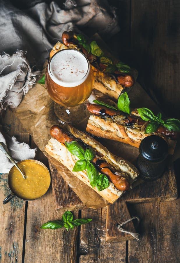 杯未过滤的啤酒和烤香肠狗在长方形宝石 免版税库存照片