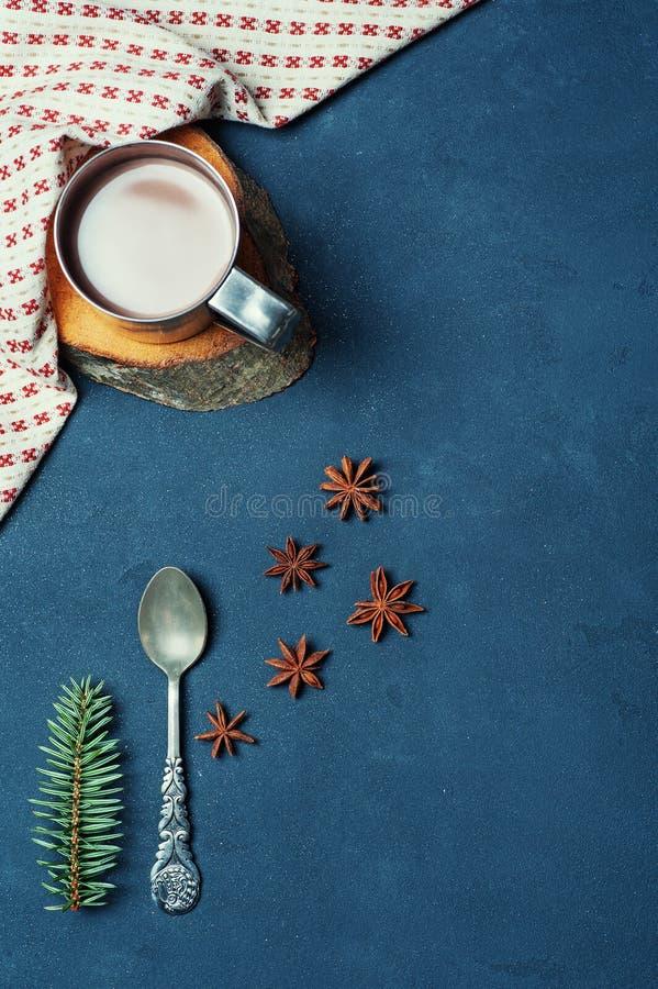 杯框架恶咖啡豆肉桂条捞出和在黑暗的纹理表装饰的餐巾的冷杉分支 厨房成份 库存照片