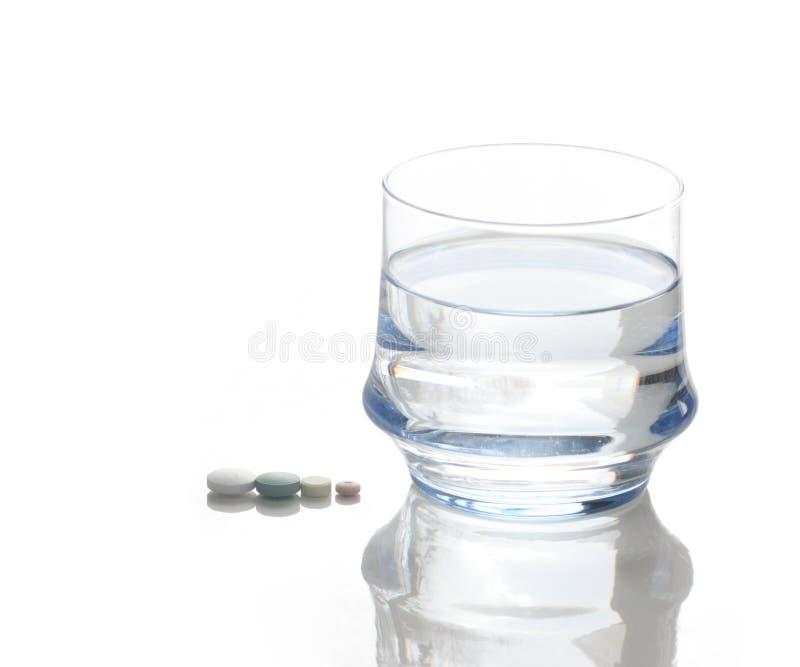 杯水和四个药片 免版税图库摄影