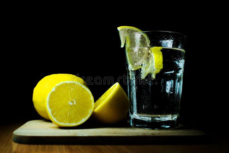 杯水和柠檬在黑背景 免版税库存图片