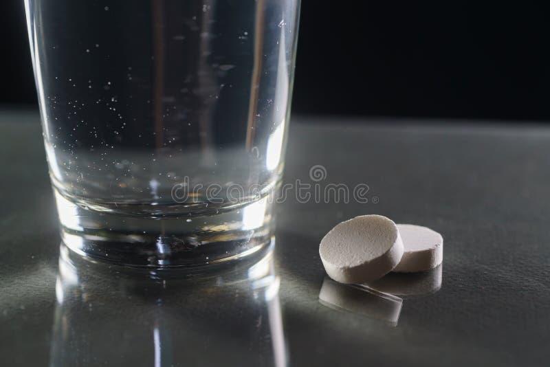 杯水和药片在黑背景 图库摄影