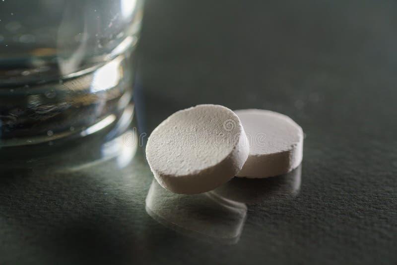 杯水和药片在黑背景 库存图片