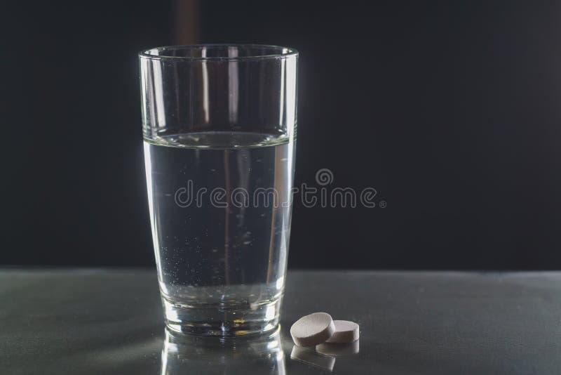 杯水和药片在黑背景 库存照片