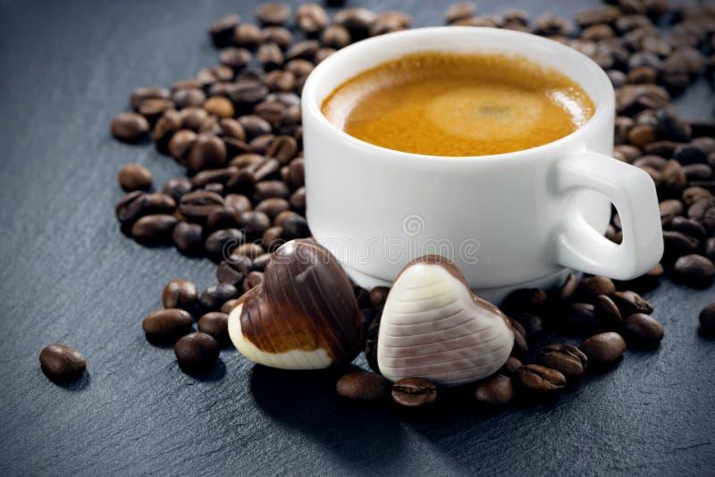 杯浓咖啡、咖啡豆背景和巧克力糖 免版税库存图片