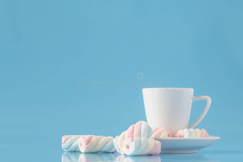 杯浓咖啡咖啡和被扭转的美国蛋白软糖在蓝色 免版税库存照片