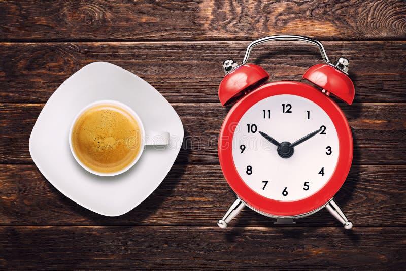 杯浓咖啡在木台式视图的咖啡和葡萄酒时钟警报 库存图片