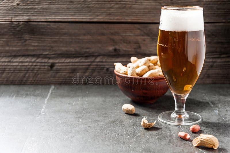 杯淡冷的泡沫的啤酒,在老木背景的坚果 库存图片