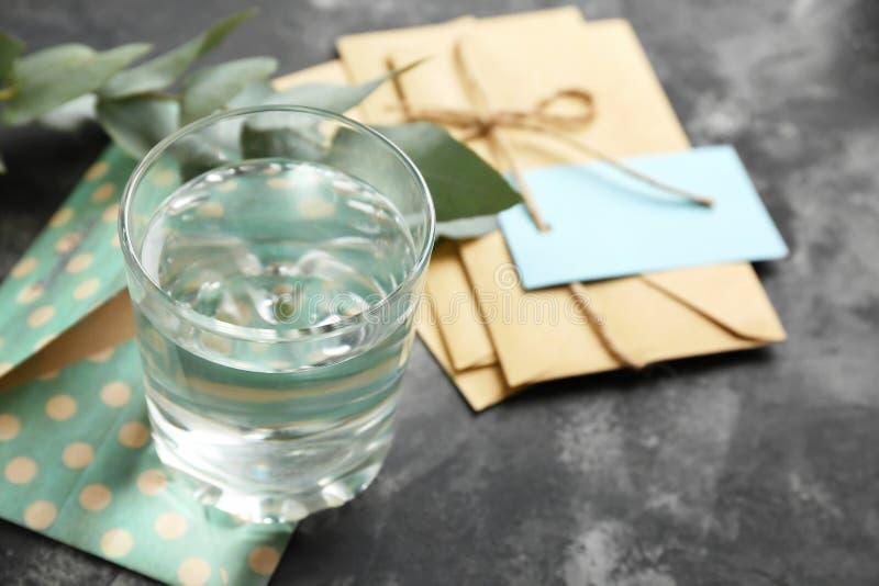杯淡水与在灰色桌上包围 库存照片