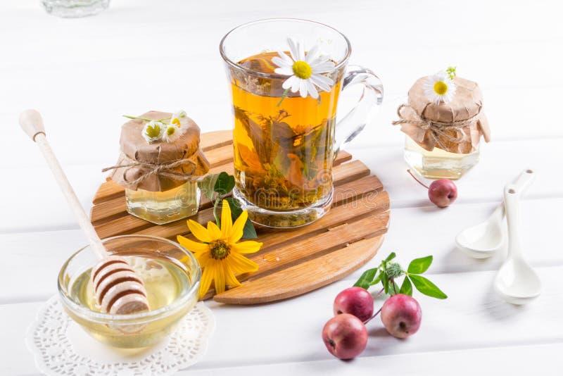杯清凉茶用自然光液体蜂蜜和野花 库存照片