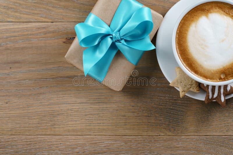 杯热奶咖啡和有天蓝色的丝带的礼物盒在木橡木桌顶视图 库存图片
