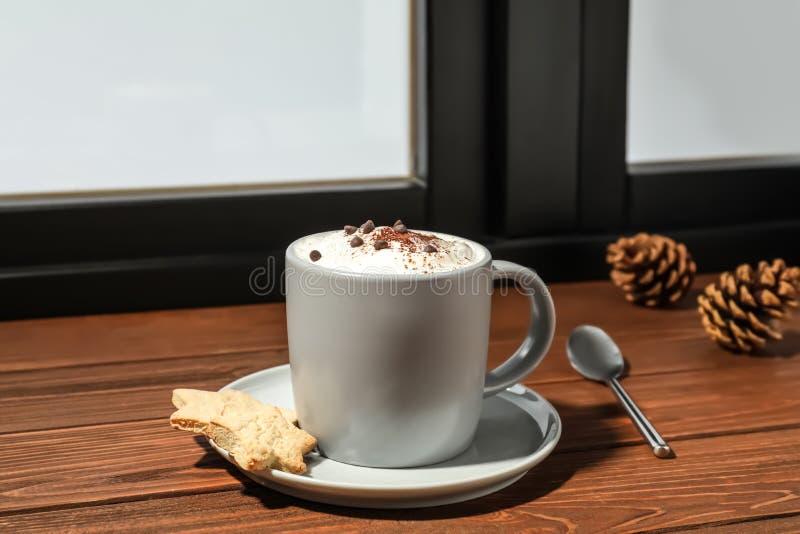 杯热奶咖啡用在窗台的曲奇饼 冬天饮料 免版税图库摄影