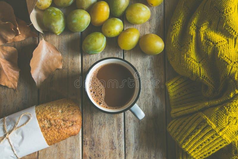杯热的可可粉、整个五谷黑麦小圆面包,疏散黄色和绿色李子在工艺纸袋 干燥叶子被编织的毛线衣,秋天 库存图片