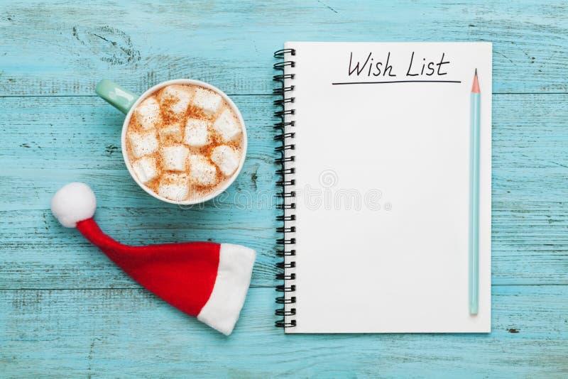 杯热的可可粉或巧克力用蛋白软糖、圣诞老人帽子和笔记本有愿望的,圣诞节计划概念 平的位置 库存照片
