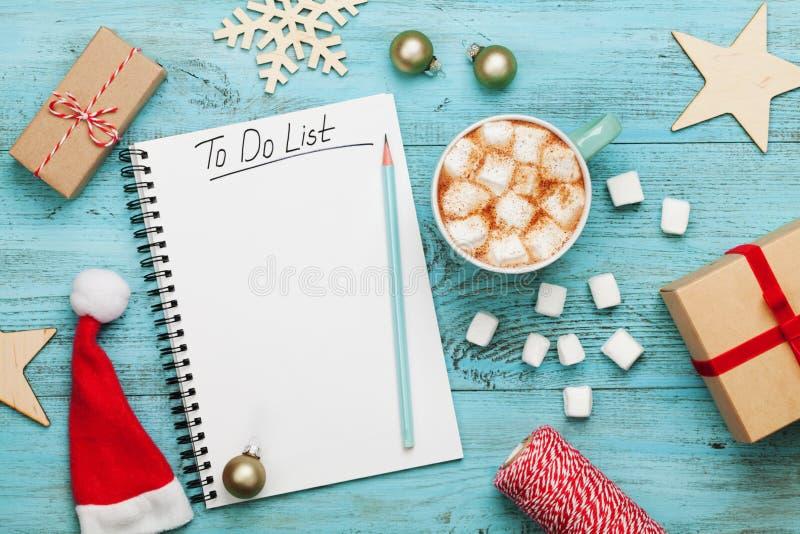 杯热的可可粉或巧克力用蛋白软糖,与要做名单的假日装饰和笔记本,圣诞节计划 平的位置 免版税库存照片