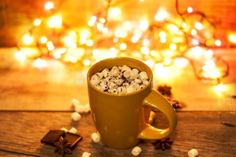 杯热的可可粉用蛋白软糖和巧克力在木背景与美好的圣诞灯 库存图片
