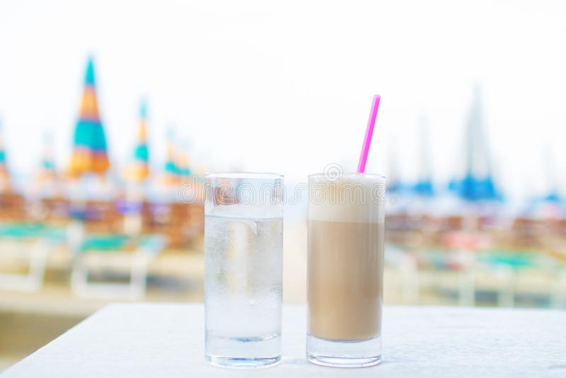 杯热的咖啡和玻璃用反对海背景的水 库存图片
