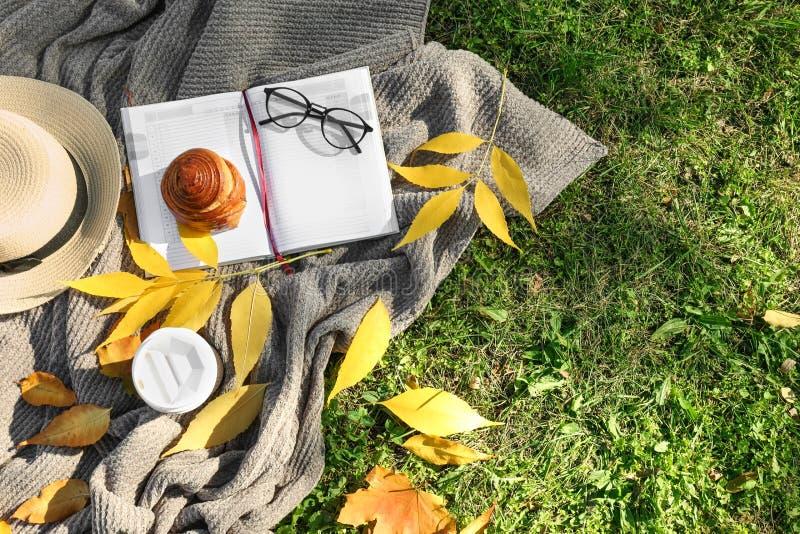 杯热的咖啡用小圆面包,笔记本和秋叶在温暖的格子花呢披肩 免版税库存图片