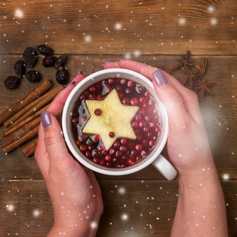 杯热的茶用莓果和苹果计算机桂香加香料拿着杯的木背景圣诞节食物概念顶视图女性手 免版税库存图片