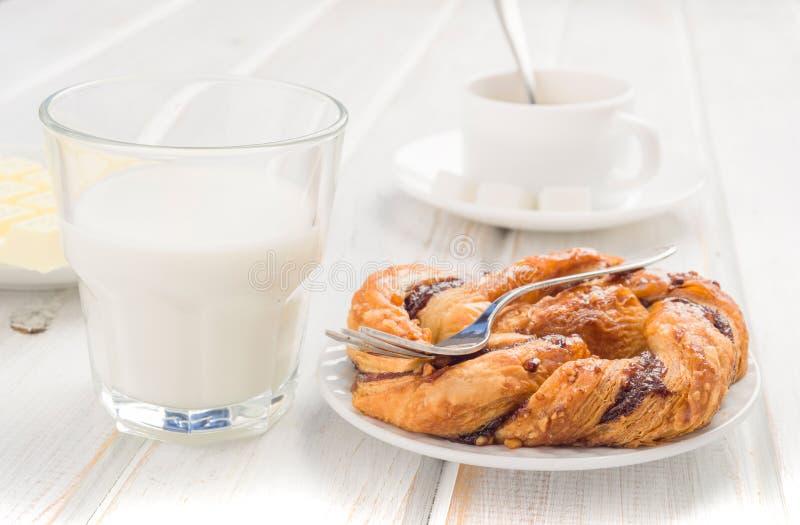 杯牛奶和吹在木头使成环 库存图片