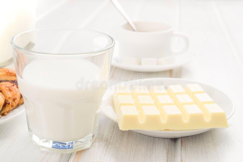 杯牛奶和巧克力块在木头 图库摄影