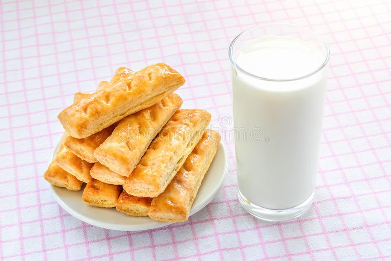杯牛奶和甜油酥点心曲奇饼在一个白色茶碟在白色桃红色方格的桌布 鲜美早餐用牛奶 免版税库存图片