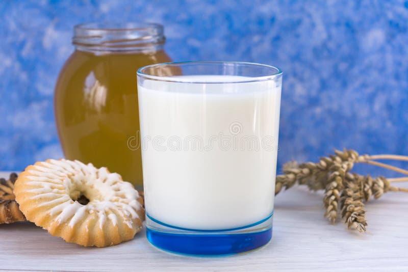 杯牛奶用曲奇饼和蜂蜜在桌上 在浅兰的背景 库存图片
