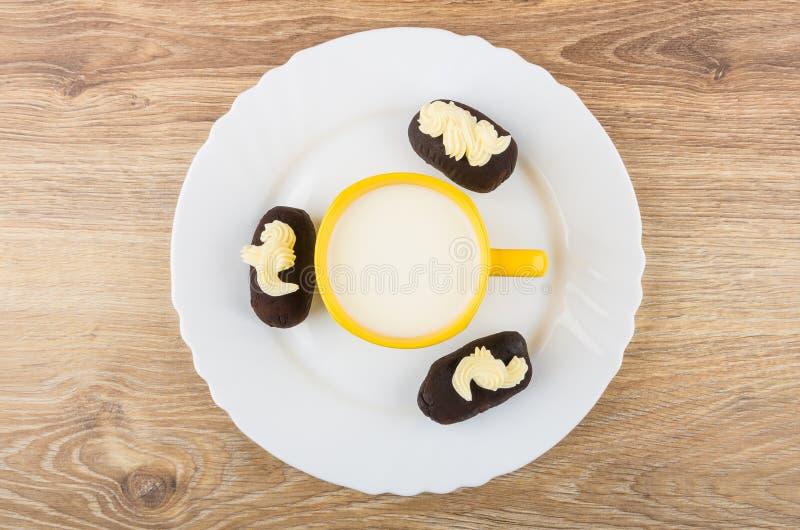 杯牛奶,巧克力饼干结块与在盘的buttercream 图库摄影