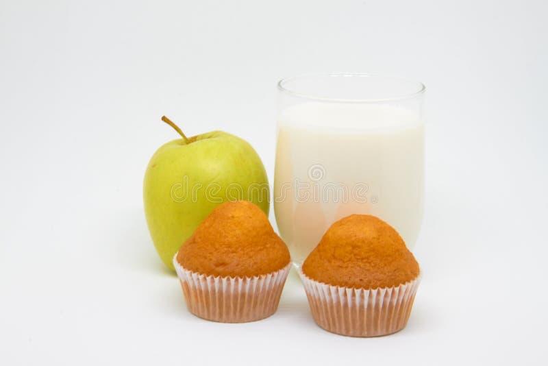 杯牛奶,果子(片断;Apple);并且杯形蛋糕 健康吃概念早餐和一个好开始对天 免版税库存图片