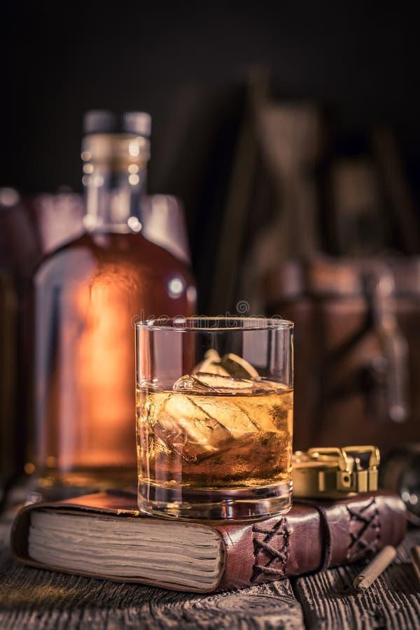 杯特写镜头与冰和金黄瓶的威士忌酒 免版税图库摄影