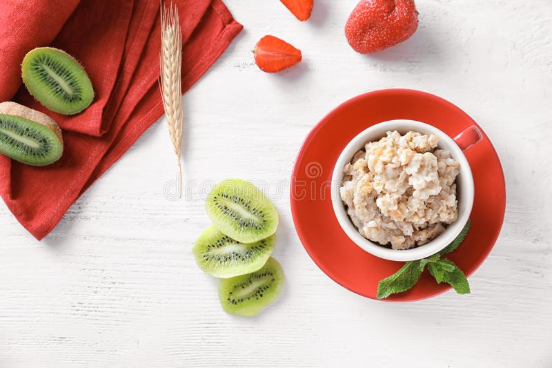 杯用鲜美燕麦粥、被切的猕猴桃和草莓在轻的背景 免版税库存图片
