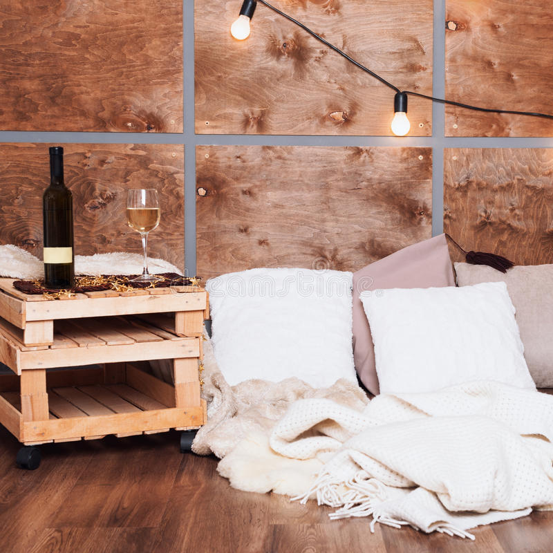 杯白葡萄酒和瓶在现代顶楼内部与轻的诗歌选在木墙壁上 免版税库存图片