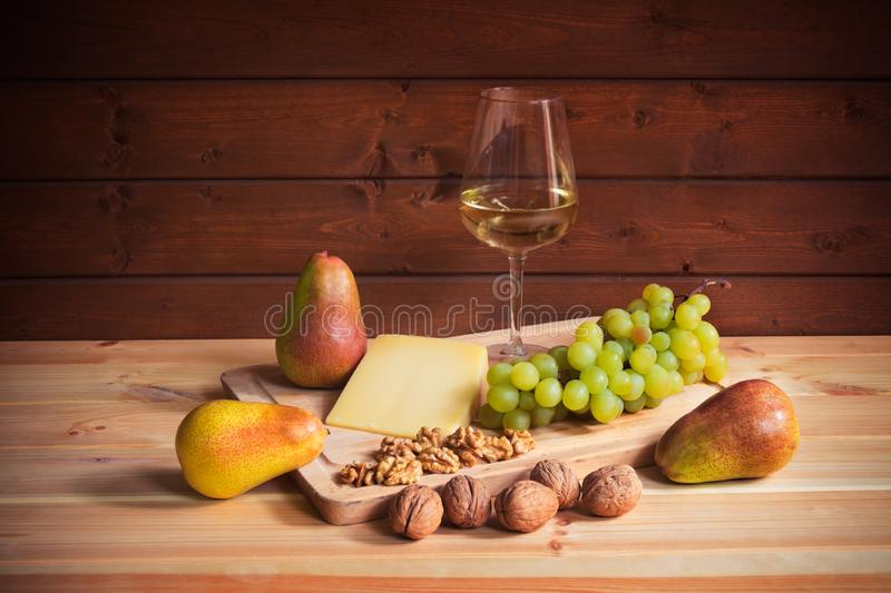 杯白酒、帕尔马干酪、核桃、梨和葡萄分支在木桌上 免版税库存图片