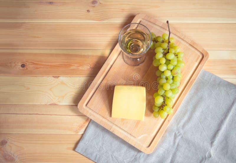杯白酒、帕尔马干酪和葡萄分支在切板在木背景 免版税库存照片