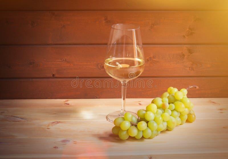 杯白酒和绿色葡萄分支在木桌上 免版税图库摄影