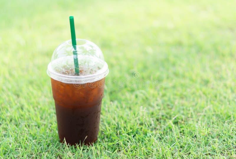 杯的关闭冰americano咖啡有绿草自然背景,选择聚焦 免版税库存图片