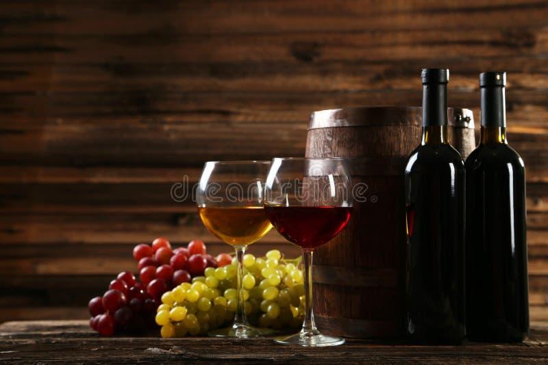 杯红色和白葡萄酒用在棕色木背景的葡萄 免版税库存图片
