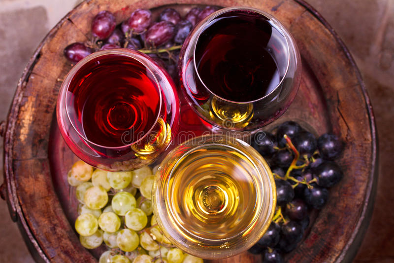 杯红色,玫瑰色和白葡萄酒用葡萄在葡萄酒库里 食物和饮料概念 免版税库存图片