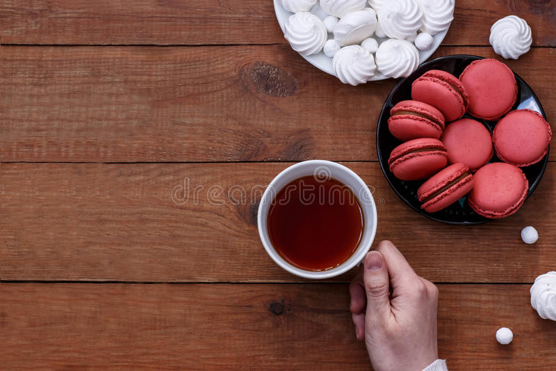 杯红茶,白色蛋白甜饼和蛋白杏仁饼干在棕色木背景 免版税库存图片