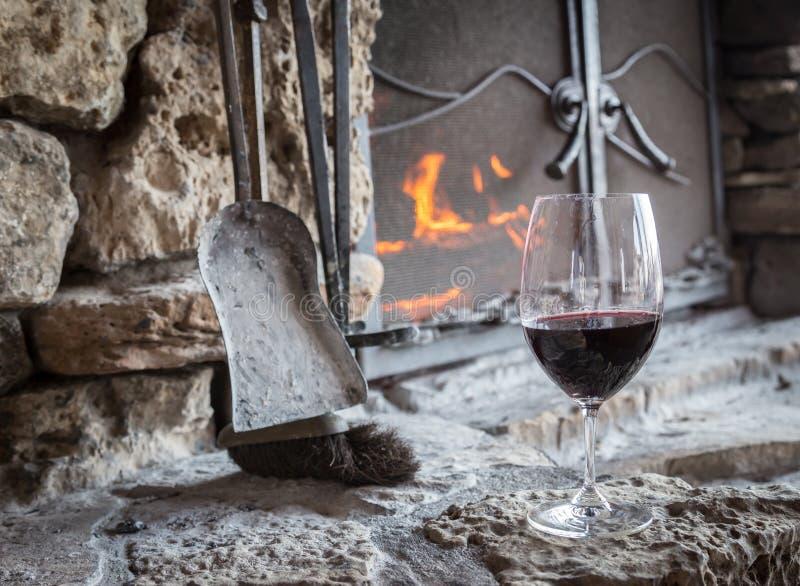 杯红葡萄酒坐在火地方前面的壁炉边 免版税库存照片